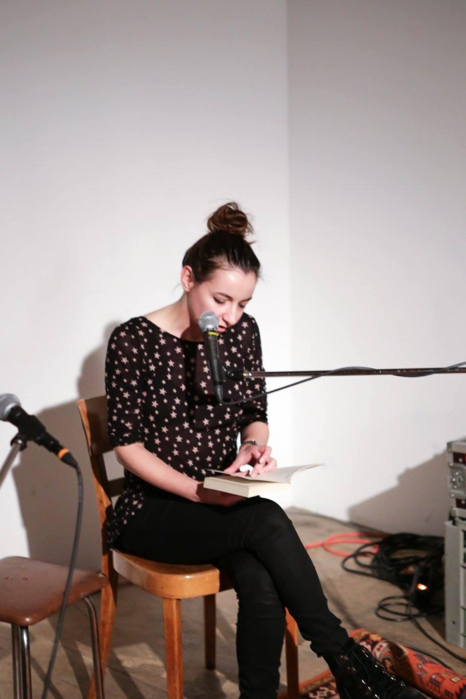 Girl in front of a microphone, reading a text
