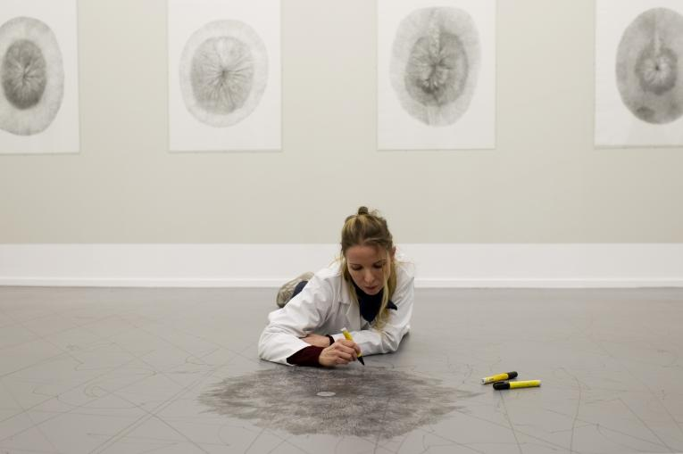 Artist lying on floor drawing