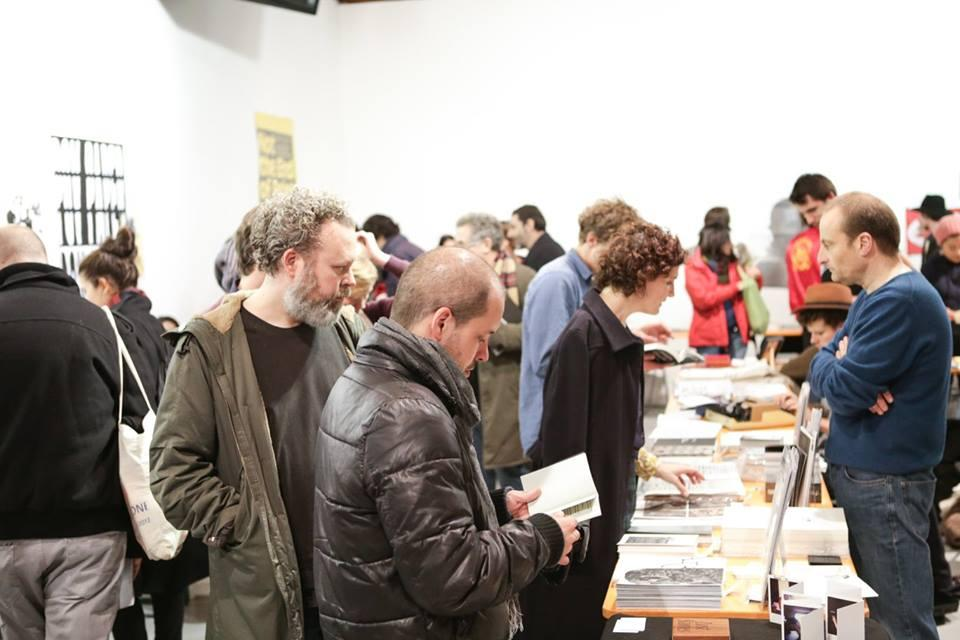 Room full of people, looking at book stands