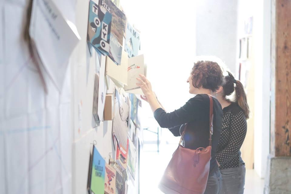 Two girls looking at publications which are hanging at a wall
