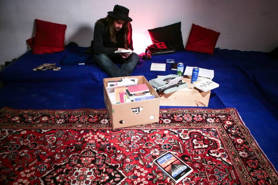 Guy sitting on a carpet with a box of books