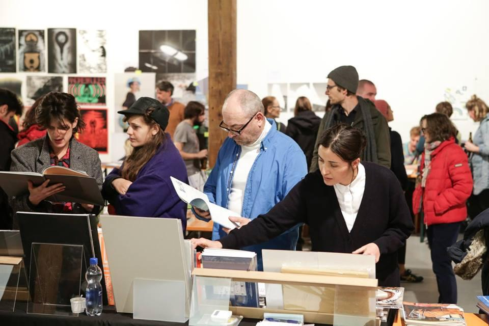 People looking at books at a book stand