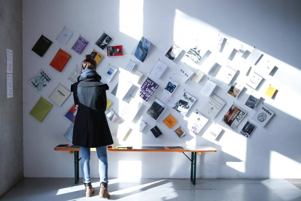 Girl standing in front of a wall with exhibited publications