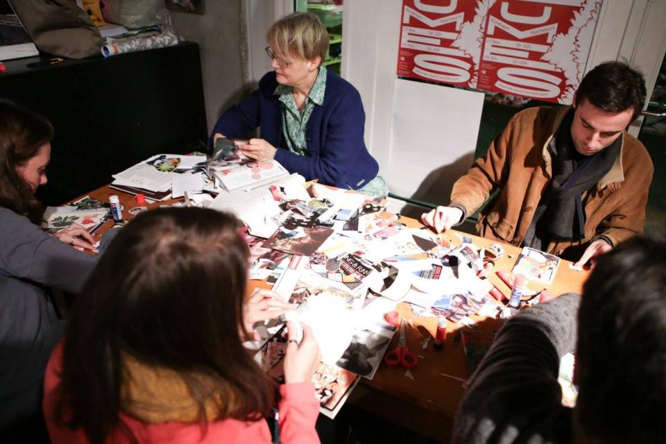 People sitting together at a table, making zines